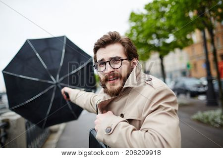 Bearded man in eyeglasses and trench-coat holding his umbrella in stormy weather