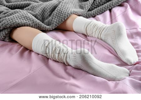 Young woman in socks lying on bed