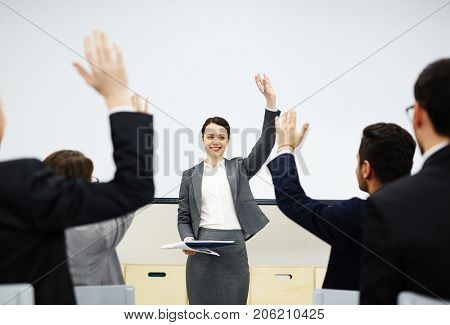 Successful teacher by whiteboard raising her hand while looking at business people ready to answer