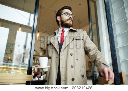 Well-dressed bearded man with glass of coffee going out of cafe after lunch