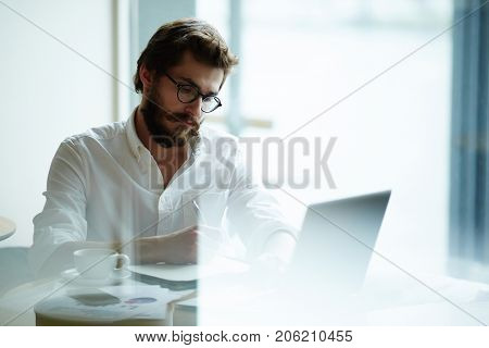 Serious man searching for job in the net or making online research
