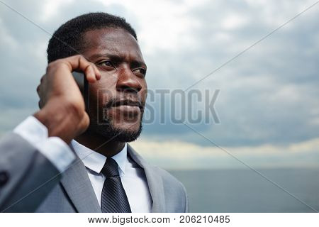 Tense businessman with smartphone calling outdoors in stormy weather