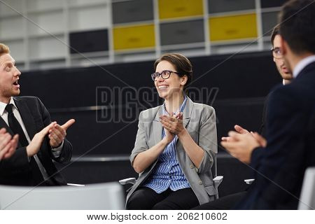 Happy professionals congratulating one of co-workers by ovations after business training