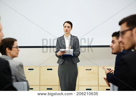 Elegant teacher making report or presentation to group of managers and discussing the topic after her speech at seminar