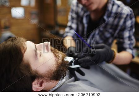 Young man having his beard shortened by professional barber