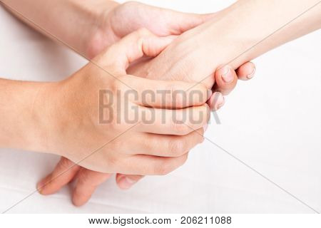 Young woman's wrist being manipulated by osteopathic manual therapist or physician