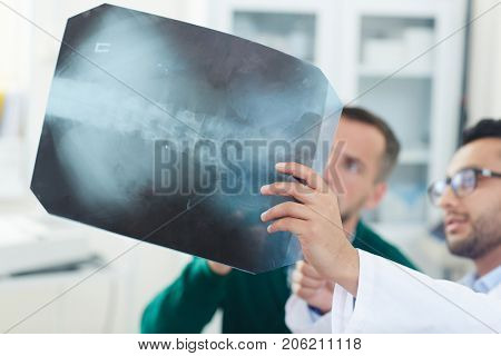 Patient and doctor looking at x-ray image and discussing problem with spinal cord