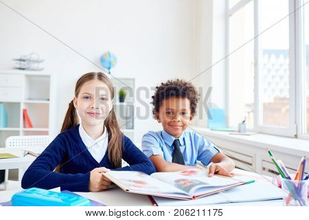 Two little classmates with open book reading in group