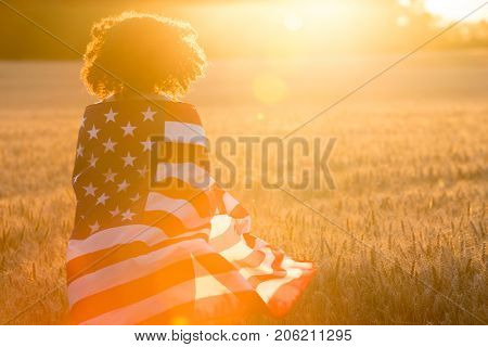 Mixed race African American girl teenager female young woman in a field of wheat or barley crops wrapped in USA stars and stripes flag in golden sunset evening sunshine