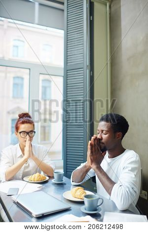 Young intercultural religious couple asking Lord to bless their food and day in the morning
