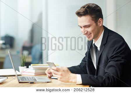 Profile view of smiling young white collar worker texting with his colleague on smartphone while sitting in front of laptop at modern office, waist-up portrait