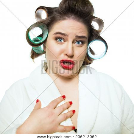 Funny emotional blue-eyed woman in dressing gown and in curlers with red lips and manicure over white background.