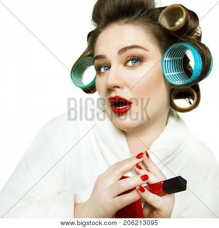 Funny portrait of blue-eyed woman in dressing gown and in curlers with red lips and manicure over white background.
