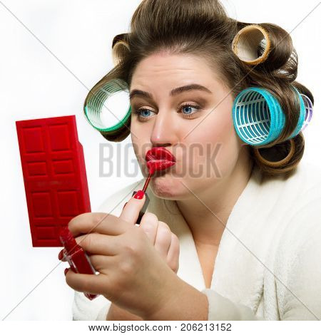 Funny portrait of blue-eyed woman in dressing gown and in curlers with red lipstick on her lips looking at the mirror over white background.