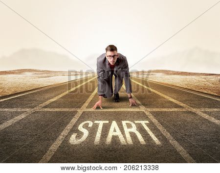 Young determined businessman kneeling before start line