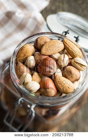 Different types of nuts in the nutshell. Hazelnuts, walnuts, almonds, pecan nuts and pistachio nuts in jar.