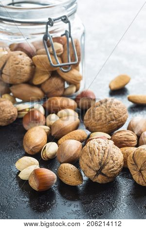 Different types of nuts in the nutshell in jar. Dried nuts.
