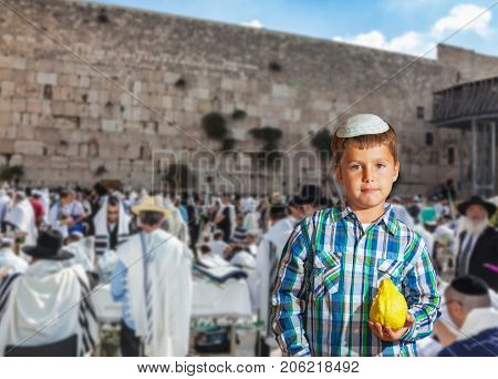People in white Taliths pray at the Western Wall of the Temple - the greatest shrine of Judaism. Autumn Jewish holiday Sukkot. Beautiful Jewish boy in white skullcap, with etrog