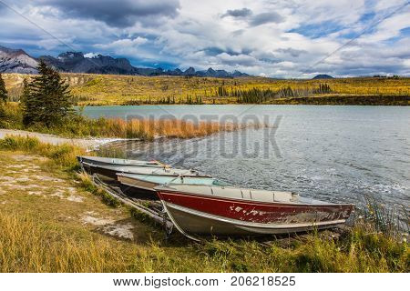 Cool autumn morning in the Rocky Mountains. Morning mist spreads over the lake. Boats on the grassy shore. Concept of active and ecological tourism