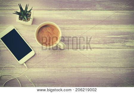 Cup of aromatic morning coffee and phone on table