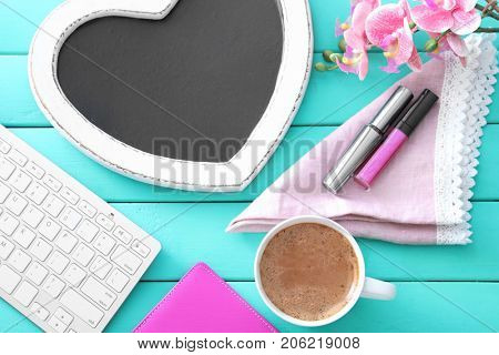 Cup of aromatic morning coffee and chalkboard in shape of heart on table