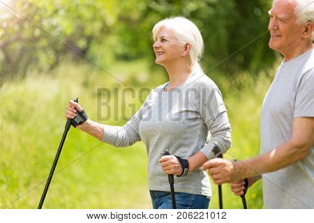 Senior couple nordic walking in park