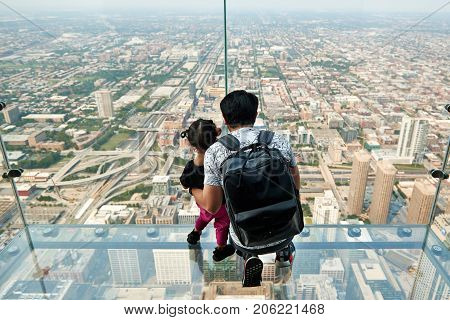 CHICAGO, IL - SEPTEMBER 2, 2017 : Father and daughter on the ledge at the Skydeck of the Willis Tower. The Skydeck is on 103rd floor of the Willis Tower, the eighth tallest building in the world.