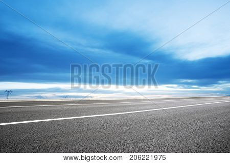emtpy asphalt road and snow mountains in blue cloud sky