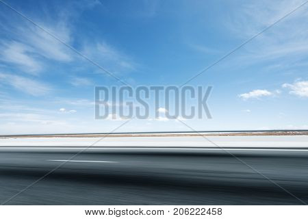 blurry emtpy asphalt road and snow mountains in blue cloud sky