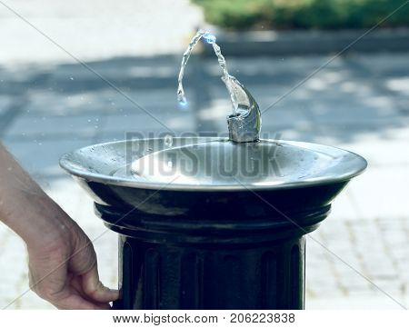 Drinking water flowing from a fountain in a city