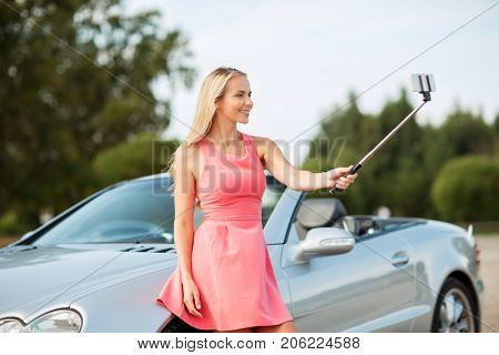 travel, road trip and people concept - happy young woman posing at convertible car and taking picture by smartphone selfie stick