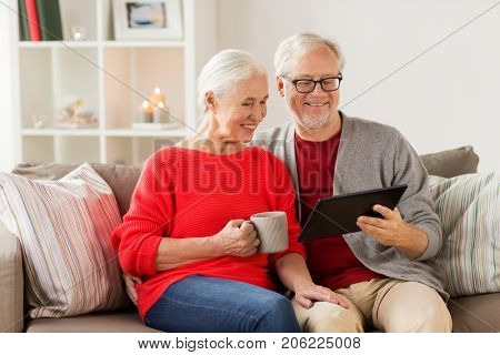 christmas, holidays and people concept - happy senior couple with tablet pc computer at home
