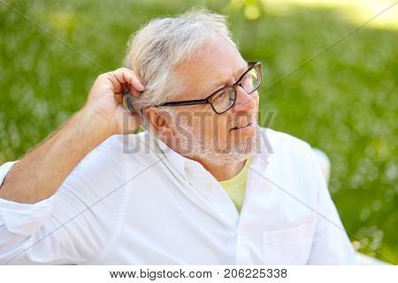 old age, retirement and people concept - happy senior man in glasses sitting at summer park