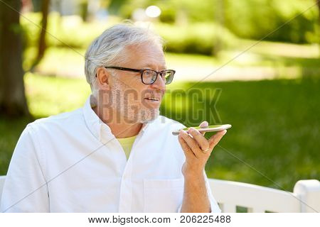 technology, senior people and communication concept - old man using voice command recorder or calling on smartphone at summer park