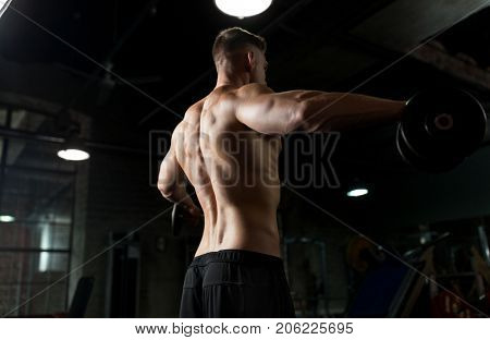 sport, bodybuilding, fitness and people concept - close up of young man with dumbbells flexing muscles in gym