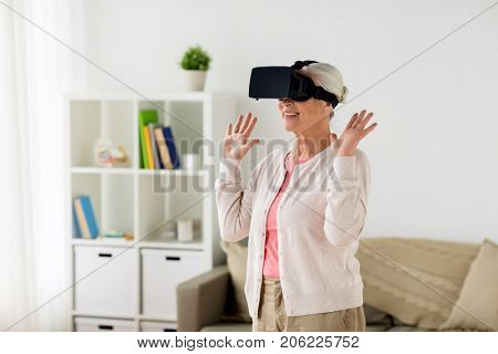 technology, augmented reality, entertainment and people concept - senior woman with virtual headset or 3d glasses playing videogame at home poster