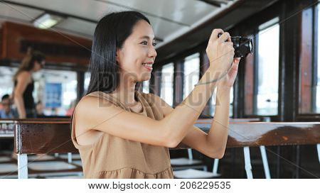 Traveler taking photo with digital camera on ferry in Hong Kong city