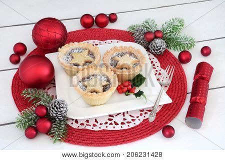 Christmas mince pies with holly on a porcelain plate with holly, silver fork, fir, cracker and red bauble decorations on distressed white wood background.