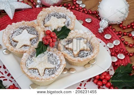 Christmas mince pie cakes on a plate with holly, bead, button  and bauble decorations on a white doilie on a red place mat.