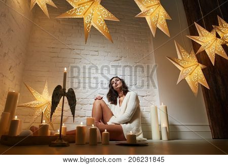 Young woman daydreaming among candles and christmas decoration at home.