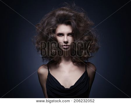 Black and white studio fashion portrait of beautiful woman with volume wavy hair. Big hair