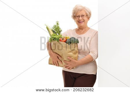 Elderly woman holding a paper bag filled with groceries and leaning against a wall isolated on white background