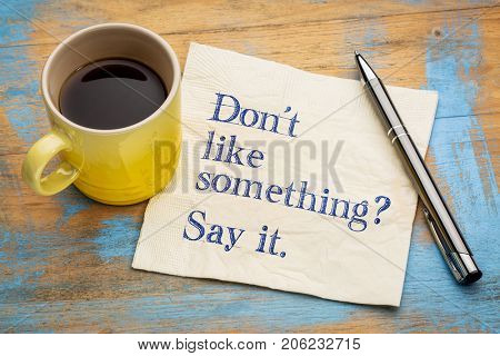 Do not like something? Say it. Handwriting on a napkin with a cup of espresso coffee
