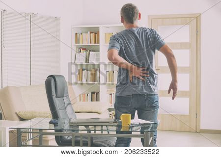 Man in home office suffering from low back pain standing near desk with notebook, papers and other objects