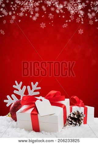 Close up of Christmas small box with red ribbon and empty greeting card. Xmas decoration with shiny ball and pine cone on snow. Christmas vertical red background.