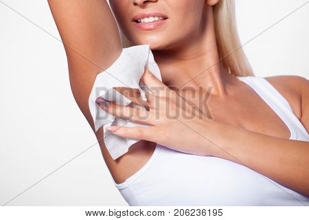 Hygiene - young woman wiping the armpit with wet wipes, perspiration, sweat poster