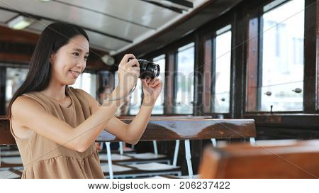 Traveler taking photo with digital camera on ferry in Hong Kong