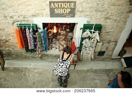 HERCEG NOVI, MONTENEGRO - JULY 15, 2017: top view of a young woman is looking at merchandise and souvenirs of a small shop in a narrow street of downtown Herceg Novi