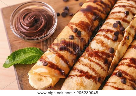 Delicious pancakes with chocolate sauce and banana on wooden board, closeup