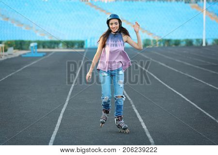 Young woman rollerskating on stadium track